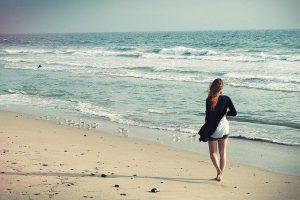 Frau spaziert barfuß am Strand